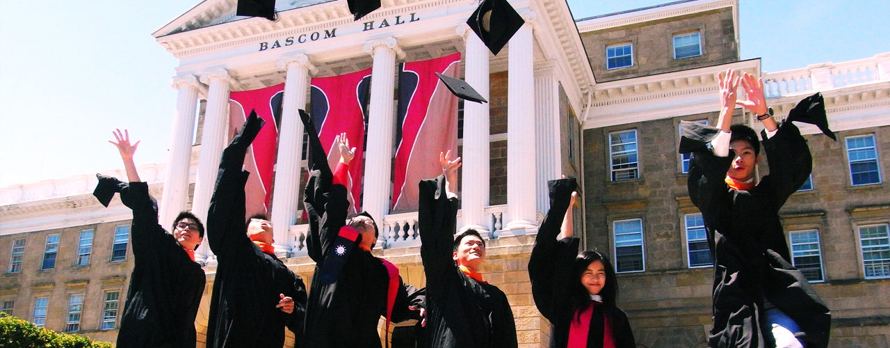 photo of students in graduation robes in front of Bascom hall