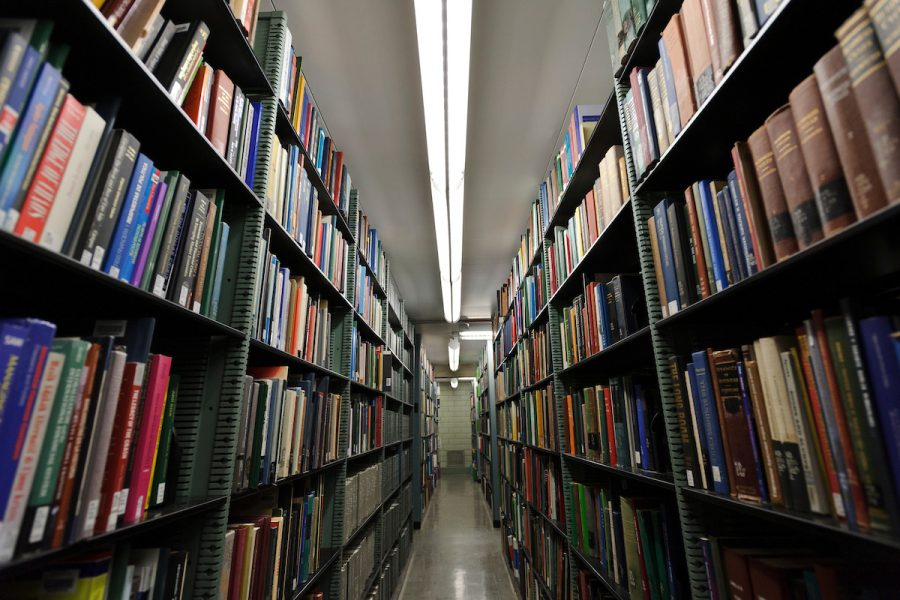 Two rows of bookshelves facing each other at Memorial Library, with a long white overhead light shining between them.