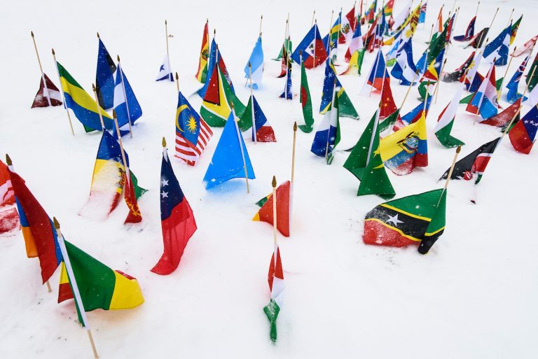 International flags -- part of a recruiting display promoting the Peace Corps -- flutter on Bascom Hill at the University of Wisconsin-Madison during a winter snowstorm with whiteout conditions on March 1, 2016. (Photo by Jeff Miller/UW-Madison)
