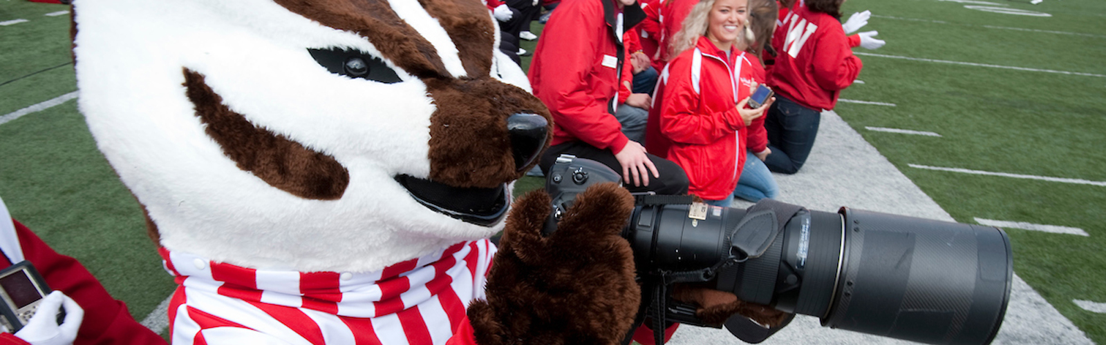 Bucky Badger takes photos of the band during a UW-Madison football game
